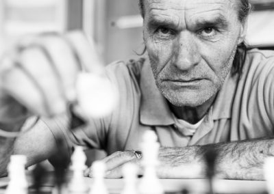 homeless man playing chess with a serious face in black and white