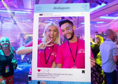 man and woman having fun at an event, holding an instagram frame