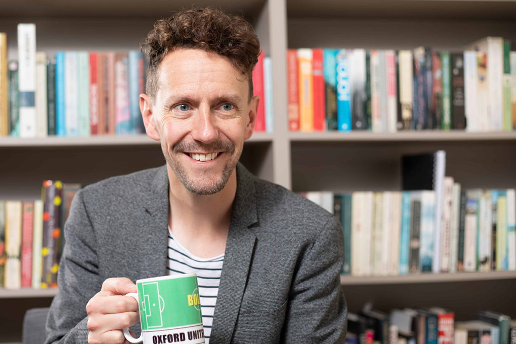 Man holding cup in front of books