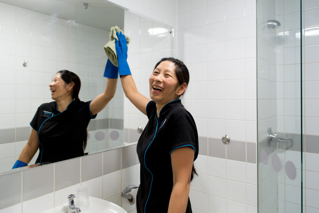 Happy woman cleaning a mirror