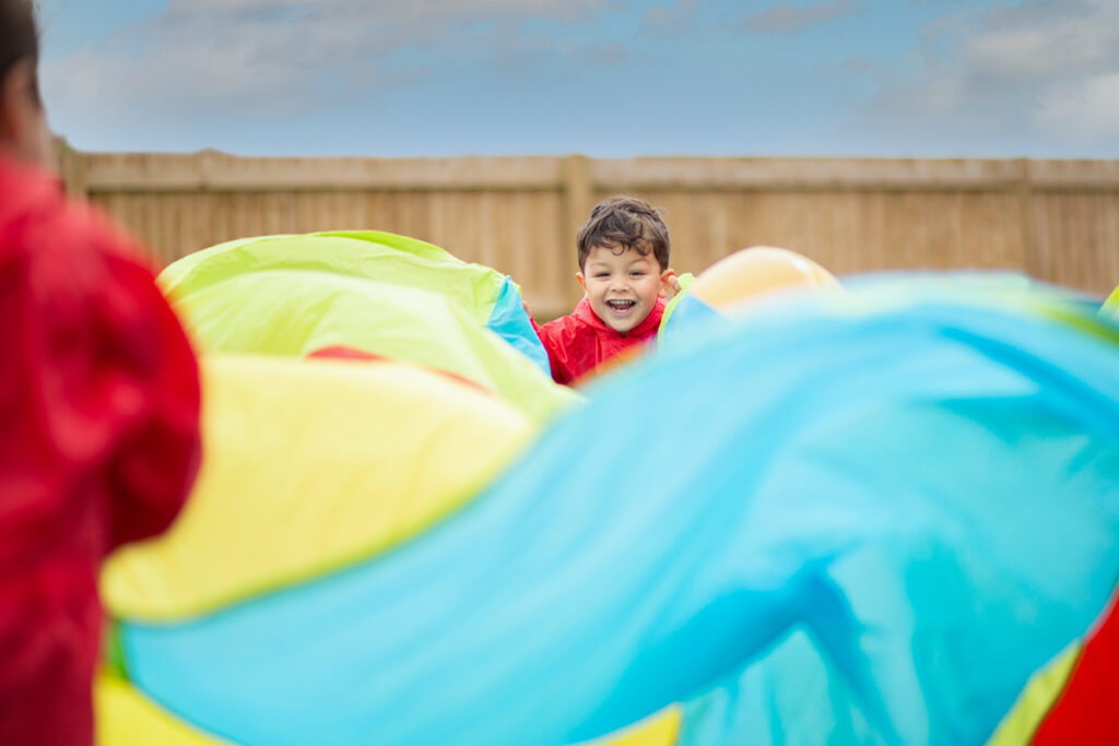 child playing with colourful parachute
