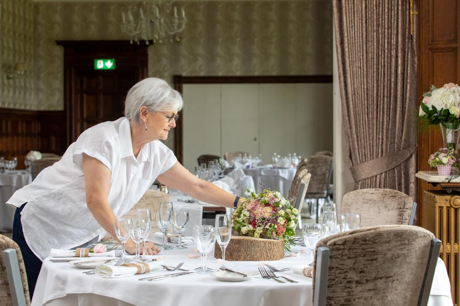 Lady setting the wedding flowers on the table